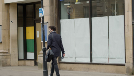 Long-Shot-of-Man-Walking-Past-Closed-Down-Shop-In-Oxford-England