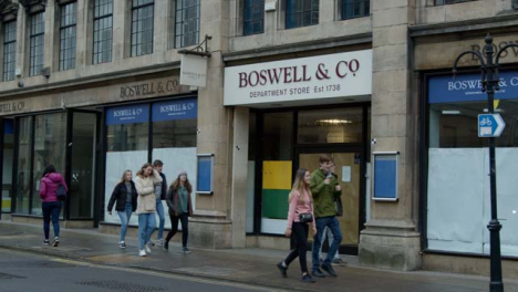 Sliding-Shot-of-People-Walking-Past-Closed-Down-Boswells-Department-Store-In-Oxford-England