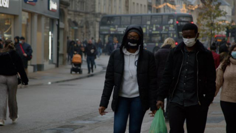 Long-Shot-of-People-In-Face-Masks-Walking-Down-a-Busy-Street-In-Oxford-England