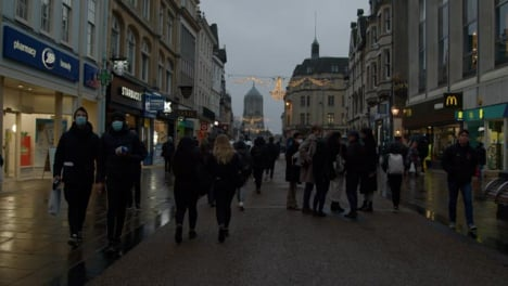 Tracking-Shot-of-People-Walking-Down-Busy-Shopping-Street-In-Oxford-England