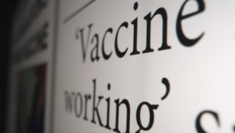 Sliding-Extreme-Close-Up-Shot-of-Covid-19-Vaccine-Article-On-a-Computer-Screen