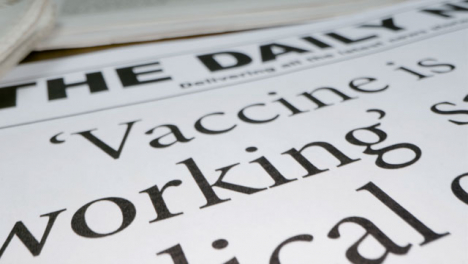 Sliding-Extreme-Close-Up-of-Newspaper-Front-Pages-with-Covid-19-Vaccine-Headlines