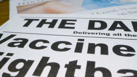 Sliding-Extreme-Close-Up-of-Newspaper-Front-Pages-with-Covid-19-Effective-Vaccine-Headlines
