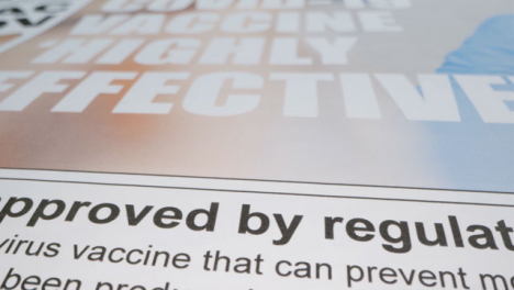 Sliding-Extreme-Close-Up-of-Some-Newspaper-Front-Pages-with-Covid-19-Effective-Vaccine-Headlines