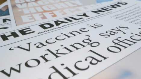 Sliding-Extreme-Close-Up-of-Pile-of-Newspaper-Front-Pages-with-Covid-19-Vaccine-Headlines