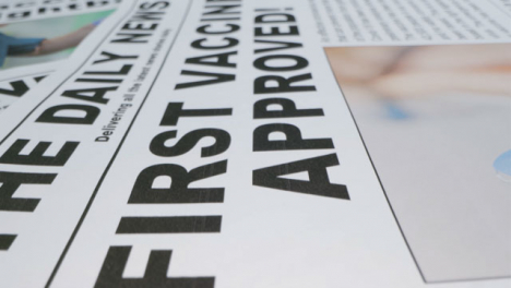 Sliding-Extreme-Close-Up-of-a-Pile-of-Newspaper-Front-Pages-with-Effective-Covid-19-Vaccine-Headlines