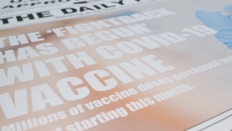 Sliding-Extreme-Close-Up-of-Newspaper-Pile-with-Effective-Covid-19-Vaccine-Headlines