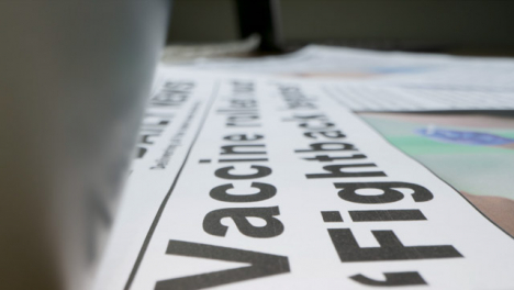 Sliding-Extreme-Close-Up-of-Pile-of-Newspapers-with-Headlines-On-Covid-19-Vaccines