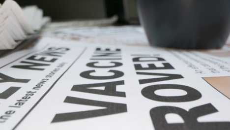Sliding-Extreme-Close-Up-of-Pile-of-Newspapers-Front-Pages-with-Headlines-On-Covid-19-Vaccines
