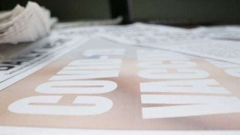 Sliding-Extreme-Close-Up-of-a-Pile-of-Newspapers-Front-Pages-with-Headlines-On-Covid-19-Vaccines