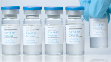 Sliding-Close-Up-Shot-of-Five-Vials-of-Covid-Vaccine-as-Hand-Takes-One-Away