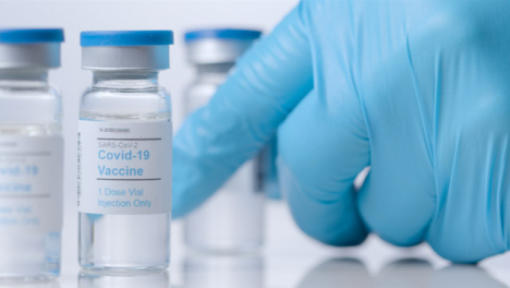 Sliding-Extreme-Close-Up-Shot-Past-Vials-of-Covid-Vaccine-As-Hand-Takes-One-Away