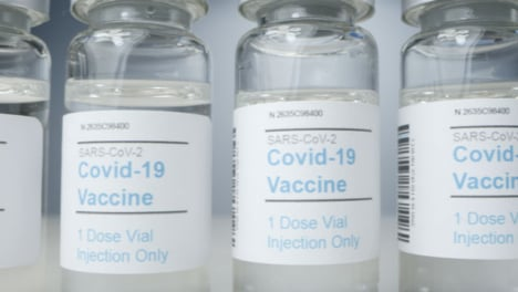 Sliding-Extreme-Close-Up-Shot-Along-Line-of-Covid-19-Vaccine-Vials
