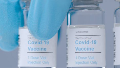 Sliding-Extreme-Close-Up-Shot-Along-Line-of-Covid-Vaccine-Vials-As-Hand-Takes-One-Away