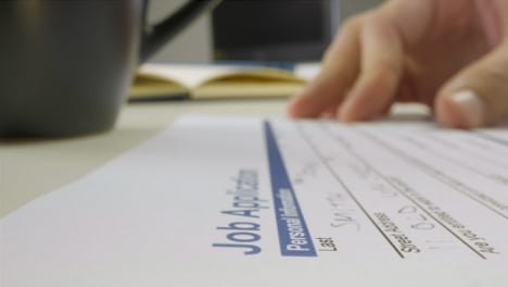 Sliding-Extreme-Close-Up-Shot-of-a-Male-Hand-Filling-Out-Job-Application-Form