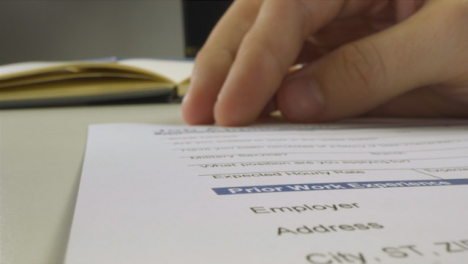 Sliding-Extreme-Close-Up-Shot-of-Male-Hand-Using-Pen-to-Read-Job-Application-Form