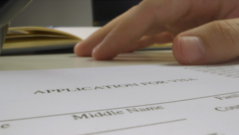 Sliding-Extreme-Close-Up-Shot-of-Male-Hand-Using-Pen-to-Read-Visa-Application-Form