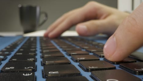 Sliding-Extreme-Close-Up-Shot-of-Male-Hands-Typing-On-Laptop-Keyboard