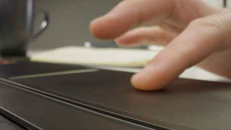 Sliding-Extreme-Close-Up-Shot-of-Male-Hands-Using-Laptop-Keyboard-and-Trackpad