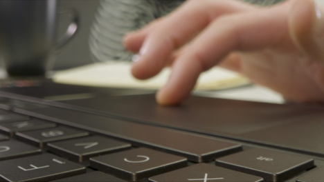 Sliding-Extreme-Close-Up-Shot-of-Male-Hands-Using-a-Laptop-Keyboard-and-Trackpad