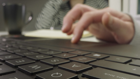Sliding-Extreme-Close-Up-Shot-of-Pair-of-Male-Hands-Drinking-Coffee-and-Using-a-Laptop