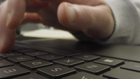 Sliding-Extreme-Close-Up-Shot-of-Pair-of-Male-Hands-Drinking-Coffee-and-Using-Laptop