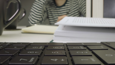 Sliding-Extreme-Close-Up-Shot-of-a-Laptop-Keyboard-and-Two-People-Reading-Books
