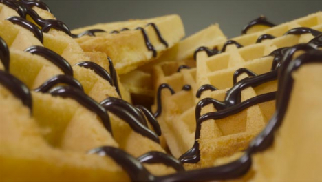 Sliding-Extreme-Close-Up-Shot-of-Chocolate-Sauce-Pouring-Onto-Waffles