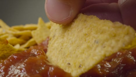 Sliding-Extreme-Close-Up-Shot-of-Nachos-Being-Dipped-Into-Spicy-Sauce-