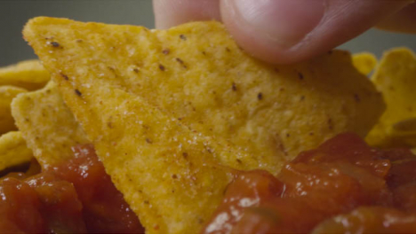 Sliding-Extreme-Close-Up-Shot-of-Some-Nachos-Being-Dipped-Into-Spicy-Sauce-