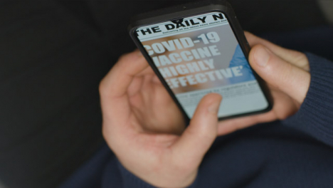 Sliding-Close-Up-of-Hands-Scrolling-COVID-Vaccine-News-Article-On-Phone