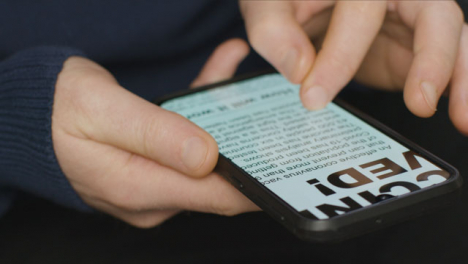 Sliding-Close-Up-of-Hands-Scrolling-COVID-Vaccine-News-Article-On-Smartphone