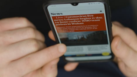 High-Angle-Close-Up-of-Hands-Scrolling-On-COVID-News-Website-On-Smartphone