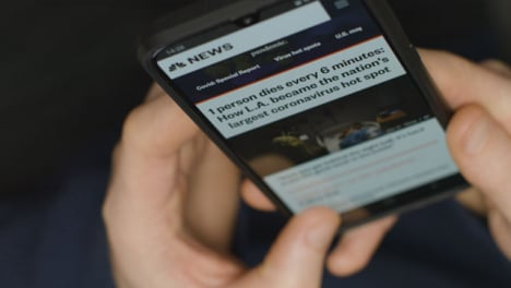 High-Angle-Close-Up-of-Hands-Scrolling-Coronavirus-News-Website-On-Smartphone