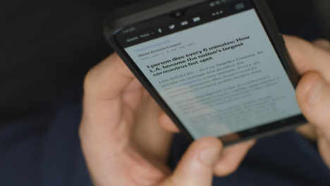 High-Angle-Close-Up-of-Hands-Scrolling-COVID-19-News-Website-On-Smartphone