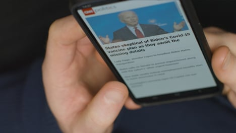 High-Angle-Close-Up-of-Hands-Scrolling-US-Politics-News-Website-On-Smartphone