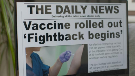 Sliding-Close-Up-of-COVID-19-Vaccine-News-Article-On-Laptop-