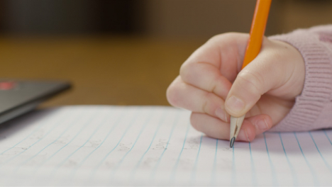 Close-Up-Shot-of-Childs-Hand-Writing-On-a-Piece-of-Paper