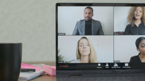 Sliding-Medium-Shot-of-Laptop-Screen-with-Four-People-In-a-Business-Video-Call