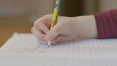 Close-Up-Shot-of-Childs-Hand-As-They-Write-On-Piece-of-Paper