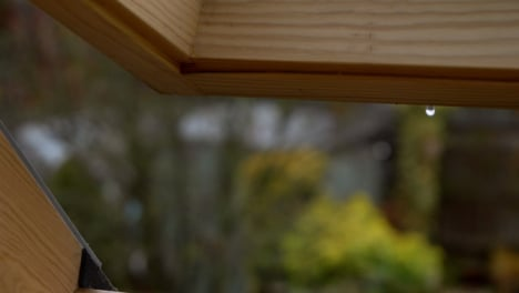 Extreme-Close-Up-Shot-of-Rainwater-Dripping-from-Open-Skylight-Window