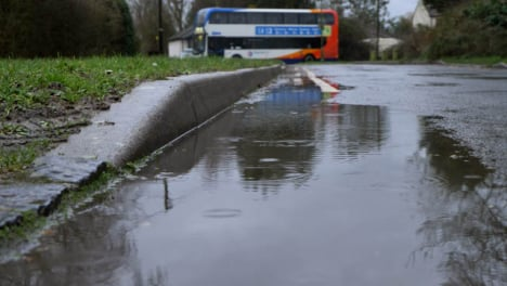 Close-Up-Shot-of-Rain-Droplets-Landing-In-Puddle-with-Traffic-In-Background