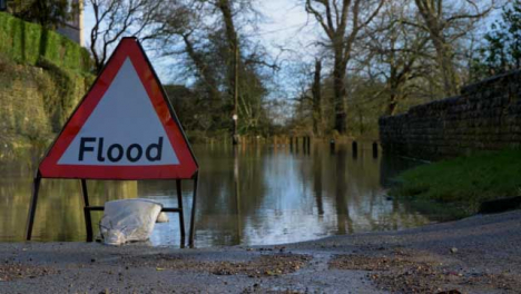 Close-Up-Shot-of-Flood-Road-Sign-In-Front-of-a-Flooded-Road