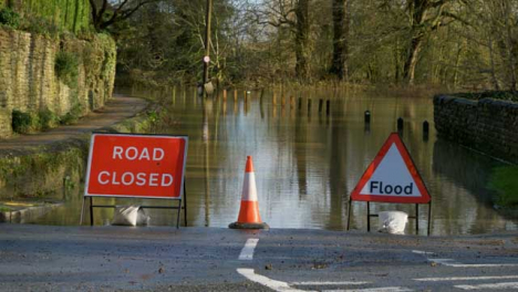 Long-Shot-of-Road-Closed-and-Flood-Signs-In-Front-of-Flooded-Street