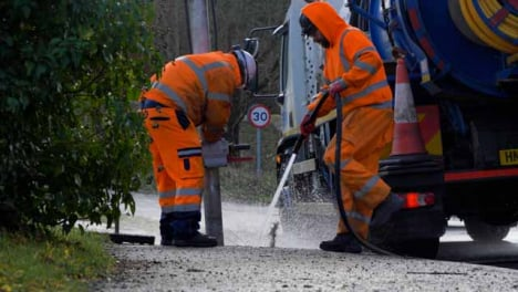 Long-Shot-of-Drainage-Workers-Attempting-to-Clear-Out-Drain-In-Flooded-Village