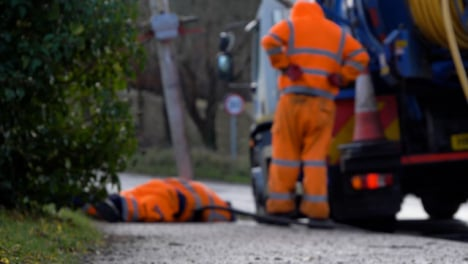 Defocused-Shot-of-Drainage-Workers-Attempting-to-Clear-Out-Drain-In-Flooded-Village