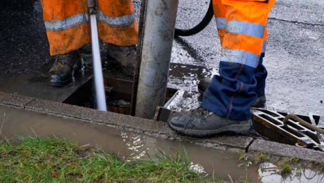 High-Angle-Shot-of-Drainage-Workers-Feet-as-They-Attempt-to-Clear-Out-Drain-