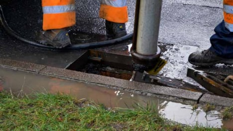 High-Angle-Shot-of-Drainage-Workers-as-They-Remove-Discarded-Car-Plate-from-Suction-Pipe