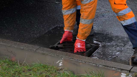 High-Angle-Shot-of-Drainage-Worker-Placing-Down-Storm-Drain-Cover