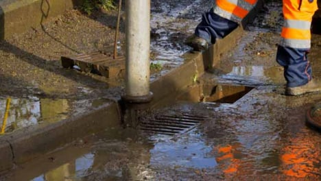 Handheld-Shot-of-Drainage-Workers-Feet-As-They-Pull-Suction-Pipe-Out-of-Blocked-Drain